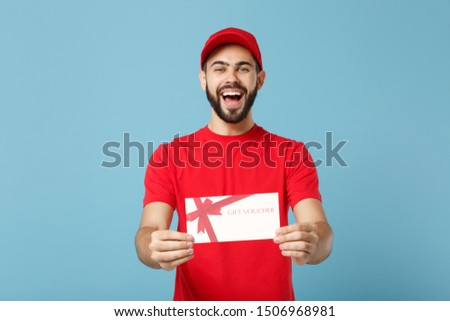 Delivery man in red workwear hold certificate isolated on blue background, studio portrait. Professional male employee in cap t-shirt print working courier dealer. Service concept. Mock up copy space