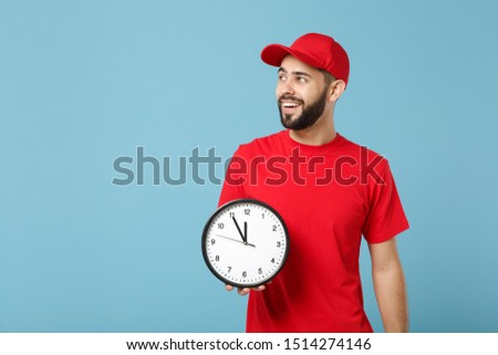 Delivery man in red workwear hold clock isolated on blue background studio portrait. Professional male employee in cap t-shirt print working as courier dealer. Service concept. Mock up copy space
