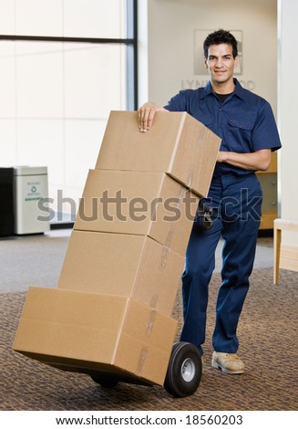 Delivery man in uniform pushing stack of cardboard boxes on dolly