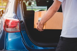 Delivery man is delivering cardboard box to customers via private car trunk door. People lifestyles and business occupation concept. Young male courier in casual clothes. Parcel move courier service