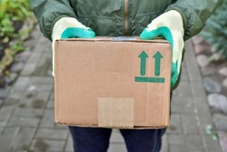 Delivery man is holding a parcel with a fragile symbol on a cardboard box. Delivery of the parcel courier service to your home. Sending fragile items by courier.