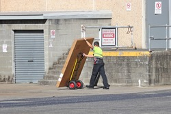Delivery man making a delivery to a back dock of a shop with a hand truck
