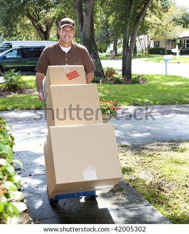 Delivery man or mover pushing a dolly loaded with boxes up the front walk.