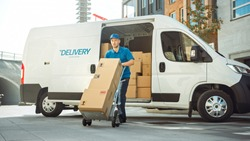Delivery Man Pushes Hand Truck Trolley Full of Cardboard Boxes Hands Package to a Customer. Courier Delivers Parcel to Man in Business District.