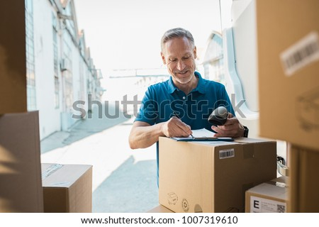 Delivery man signing checklist and holding scanner in hand. Happy courier writing on clipboard and scanning barcode. Mature man updating checklist of delivery in van.