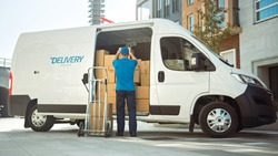 Delivery Man Uses Hand Truck Trolley Full of Cardboard Boxes and Packages, Loads Parcels into Truck / Van. Professional Courier / Loader helping you Move, Delivering Your Purchased Items Efficiently