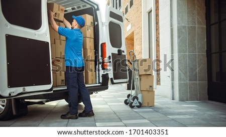 Delivery Man Uses Hand Truck Trolley Full of Cardboard Boxes and Packages, Loads Parcels into Truck / Van. Professional Courier / Loader helping you Move, Delivering Your Purchased Items Efficiently Foto d'archivio ©