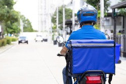 Delivery man wearing blue uniform riding motorcycle and delivery box. Motorbike delivering food or parcel express service