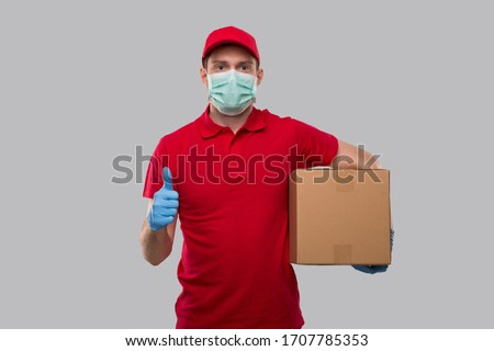 Delivery Man Wearing Medical Mask and Gloves Holding Box Showing Thumb Up. Delivery Boy with Box in Hands Smiling. Home Delivery.