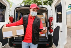Delivery man with package and smartphone or digital scanner while wearing protective face mask at work - Transportation in the backgound