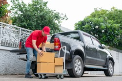 Delivery men in red uniform unloading cardboard boxes from pickup truck. Courier man sending the parcel or package to the customer on a business day. Online shopping and transport logistics concept.
