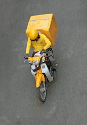 Delivery of consignments on motorbike. Motorcyclist rides with delivery in the large yellow box on street Ho Chi Minh city, Vietnam.
