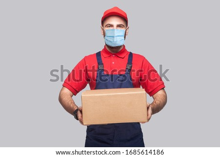 Delivery on quarantine. Portrait of young man with surgical medical mask in blue uniform and red t-shirt standing and holding the cardboard box on grey background. Indoor, studio shot, isolated,