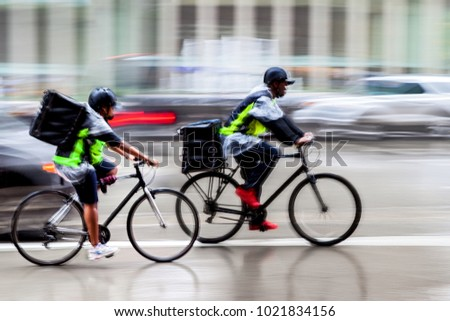 delivery on the bike in traffic on the city roadway  motion blur in the rain