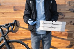 Delivery person standing next to a bicycle holds pizza boxes and a phone. Job as a courier, bike messenger profession, part time work concept
