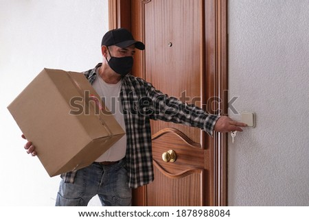Delivery senior man ringing the door bell holding a package. 'Muy fragil' means very fragile. Delivery service under quarantine, disease outbreak, coronavirus covid-19 pandemic conditions. Foto stock ©