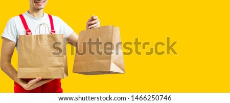 delivery service, fast food and people concept - happy man with coffee and disposable paper bag yellow background