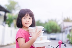 Delivery service,Takeaway, Food delivery and Stay at home safe lives from Covid19 Coronavirus.Little asian girl holding go box food with hungry.Delivering Food In City.Delivery food service from home.