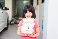 Delivery service,Takeaway, Food delivery and Stay at home safe lives from Covid19 Coronavirus.Little asian girl holding go box food with hungry.Home Delivering Food.Delivery food service from home.