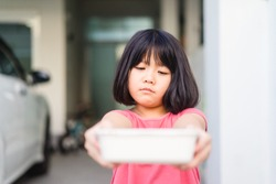Delivery service,Takeaway, Food delivery and Stay at home safe lives from Covid19 Coronavirus.Little asian girl holding go box food with hungry and bored. Bad and slow Delivery food service from home.