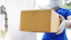 Delivery services courier during the Coronavirus (COVID-19) pandemic, close-up of cardboard box holding by a courier wearing protective face mask and latex gloves at home front door blurred background