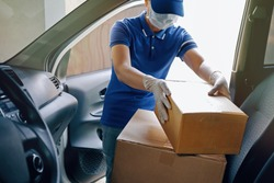 Delivery services courier during the Coronavirus (COVID-19) pandemic, courier wearing medical mask and latex gloves for safety protection from virus infection working with cardboard boxes on van seat.