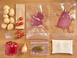 Delivery set of packaged food for dinner. meat in plactic bag and vegetables: potatoes, onions, spices, cherry tomatoes, red pepper on wooden table background