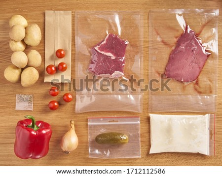 Delivery set of packaged food for dinner. meat in plactic bag and vegetables: potatoes, onions, spices, cherry tomatoes, red pepper on wooden table background Photo stock ©