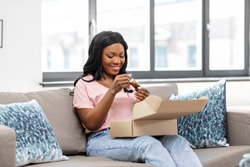 delivery, shipping and people concept - happy young african american woman opening parcel box with cosmetcis at home
