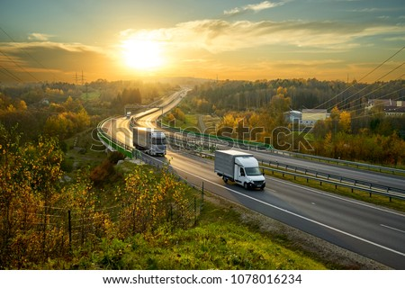 Delivery van and truck driving on the highway winding through forested landscape in autumn colors at sunset #1078016234