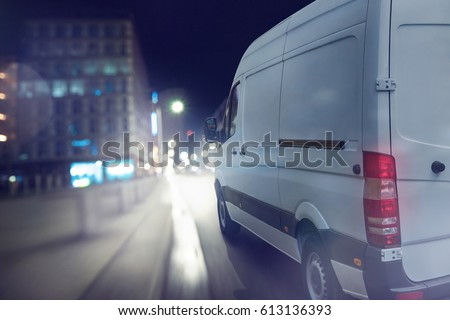 Delivery van drives at night in a city