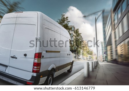 Delivery van drives through a city in the day