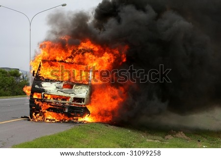 Delivery vehicle ablaze on the side of the road way - stock photo