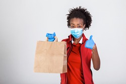 Delivery woman employee in red t-shirt uniform mask glove hold craft paper packet with food isolated on white background studio Service quarantine pandemic coronavirus virus 2019-ncov concept