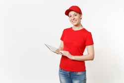 Delivery woman in red uniform isolated on white background. Female in cap, t-shirt, jeans working as courier or dealer, holding tablet pc computer with blank empty screen. Copy space advertisement