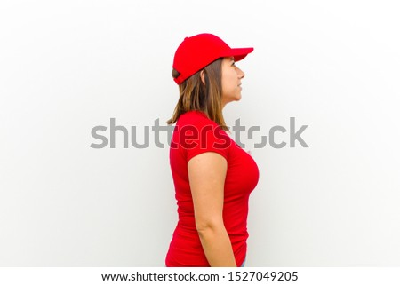 delivery woman on profile view looking to copy space ahead, thinking, imagining or daydreaming against white background #1527049205