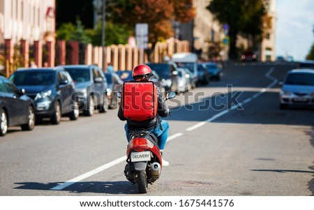 Deliveryboy on scooter with red backpack driving fast to customers, online orders. Courier delivering food on motorbike. Food supplier driving fast on motorcycle. Quick deliver food to customers