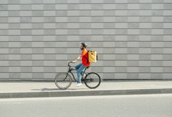 Deliveryman on bicycle. Young guy with beard and big backpack rides along path in city on gray brick wall background, side view, free space
