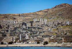 Delos the sacred Cycladic island Greece. There where archaeology meets history and mythology. Ruins of ancient civilization at seaside. Stonewalls marble columns sandy beach summer destination explore