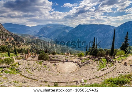 Delphi, Phocis / Greece. Ancient Theater of Delphi. The theater, with a total capacity of 5,000 spectators, is located at the sanctuary of Apollo. Panoramic view on a sunny day with cloudy sky