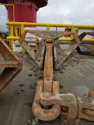 Delta flipper anchor stowed on deck of a construction work barge