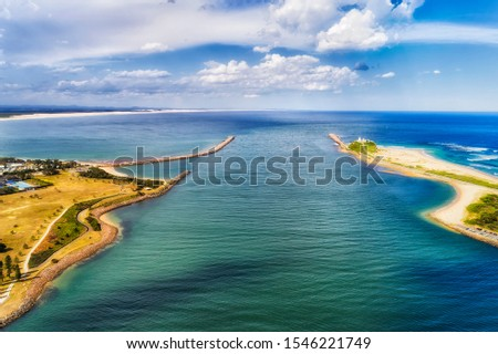 Delta of Hunter Valley entering pacific ocean off Newcastle city along distant Stockton beach between capes and breakwater walls forming path for cargo ships - aerial view to open sea over water. #1546221749