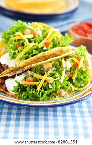 Deluxe hard shelled beef tacos served with salsa #82801351