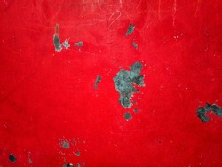 Demak, Indonesia. September 2, 2021. On a red room wall with chalk streaks, some of which are blotched and peeling.