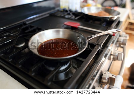 Demi glace or brown glaze cooking in a stainless steel skillet on the stove top. Photo stock ©
