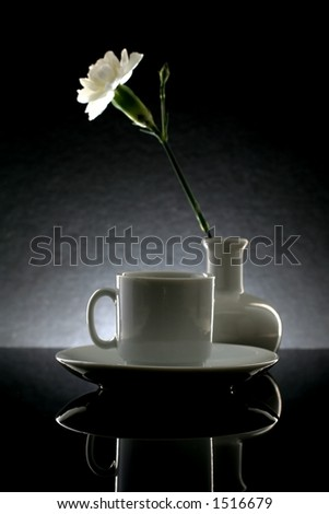 Demitasse cup,saucer,vase and flower against black background.