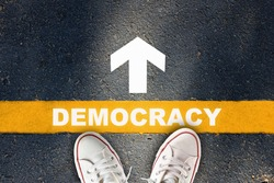 Democracy written on yellow line with white arrow on asphalt road. Future ahead concept