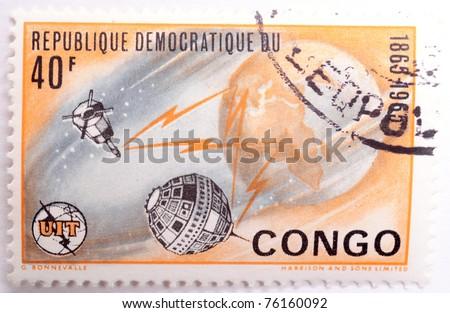 DEMOCRATIC REPUBLIC OF CONGO - CIRCA 1965: a stamp from the Democratic Republic of Congo shows image of the Earth and satellites, circa 1965 - stock photo