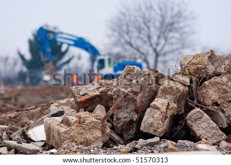 Demolishing site. Bricks of the demolished building on the foreground and defocused excavator on the background.