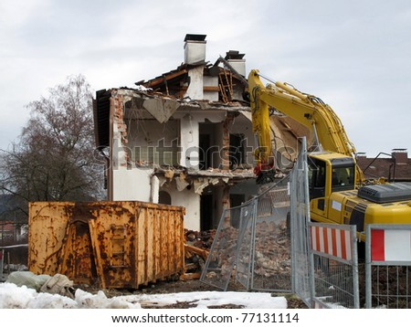 Demolition, construction. Crane dismantling building. - stock photo